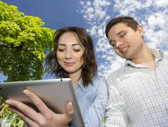 Man and woman with tablet PC on blue sky background Stock Photos