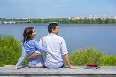 Young couple on parapet looking sideward - stock photo