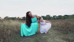 Mother and her little daughter showing their dresses on the autumn field Stock Footage