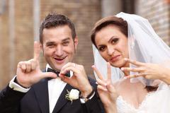 Portrait of bride and groom making love sign with hands - stock photo
