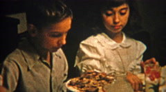 1951: Brother and sister sharing food at the dinner table. Stock Footage