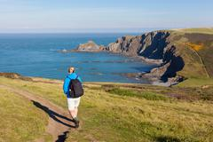 Woman Walking Coast Path Near Hartland Quay - stock photo