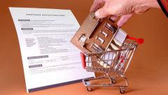 Stock Video Footage of UK mortgage application form with model house and shopping trolley.