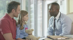 4K Friendly doctor talking to parent and child patient in office - stock footage