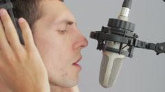 Man in headphones singing at studio microphone Stock Footage