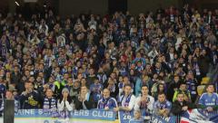 People at the stadium during a football match. People, crowd, football fans - stock footage