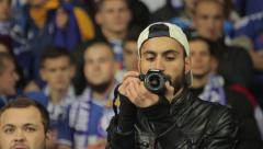 The man at the stadium taking pictures during the match. People, crowd, football - stock footage