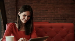 woman using tablet computer touchscreen and smiling in cafe - stock footage