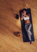 Fitness woman lying on mat using mobile phone Kuvituskuvat