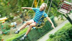 Сhild teen boy rides a big old carousel in the park Stock Footage