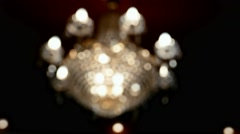 Large, illuminated crystal chandelier on the ceiling in defocus Arkistovideo