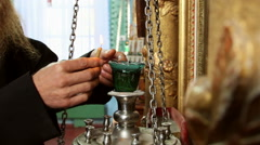 Old rite christian monk who lights a candle Stock Footage