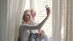 Blonde mother and daughter taking selfie Stock Footage