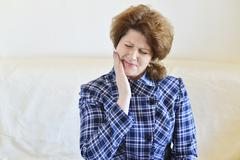 Young woman in pain is having a toothache Stock Photos