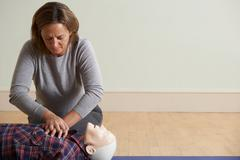 Woman Using CPR Technique On Dummy In First Aid Class Stock Photos