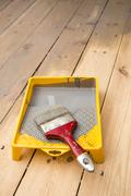wooden plank floor varnishing. gray varnish and paintbrush in tray - stock photo