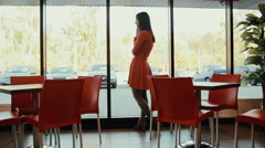 Women talks on the phone near the window in cafe. in full growth Stock Footage