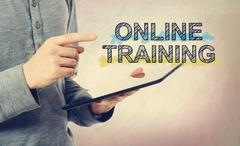 Young man pointing at Online Training text over tablet computer - stock photo