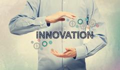 Young man in blue shirt holding Innovation - stock photo