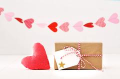 A garland of hearts above a small gift-wrapped box and red textile heart on a - stock photo