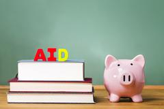 Student aid theme with textbooks and piggy bank Stock Photos