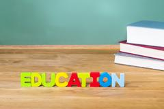 Education theme with textbooks and green chalkboard Stock Photos