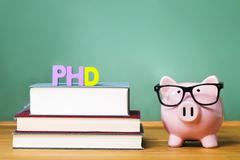 PhD degree theme with textbooks and piggy bank with glasses - stock photo