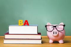 Bachelor of Arts degree theme with textbooks and piggy bank - stock photo