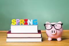 Spring Semester theme with textbooks and piggy bank Stock Photos