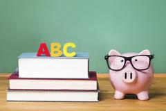 School theme with ABCs and pink piggy bank with chalkboard in the background Stock Photos