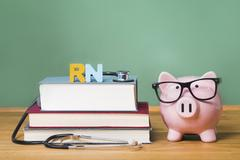 Registered Nurse RN theme with pink piggy bank with chalkboard - stock photo