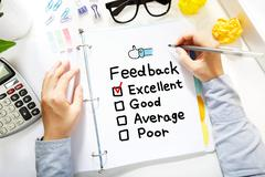 Person drawing Feedback concept on white paper - stock photo