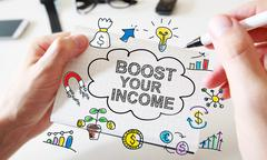 Mans hand drawing Boost Your Income concept on notebook - stock photo