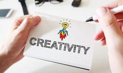 Mans hand drawing Creativity concept on notebook - stock photo