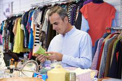 Male Shopper In Thrift Store Looking At Ornaments - stock photo