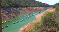 Houseboats sit low in the water at Oroville Lake in California during extreme Stock Footage