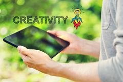 Creativity concept with young man holding his tablet - stock photo
