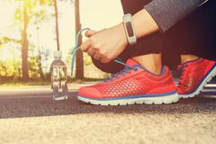 Female jogger tying her running shoes - stock photo