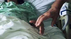 Man's hands holding woman's hands as she lays down in hospital bed - stock footage