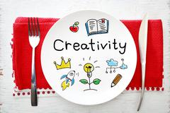 Creativity concept on white plate with fork and knife - stock photo