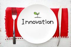 Innovation concept on white plate with fork and knife - stock photo
