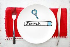 Search concept on white plate with fork and knife - stock photo