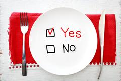 Yes or No concept on white plate with fork and knife Stock Photos