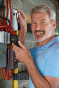 Portrait Of Man Taking Electricity Meter Reading - stock photo