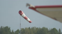Red-white windsock flutters in the wind on a field near small aircrafts. Stock Footage