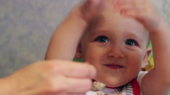 Mom feeds the baby cheerful spoon Stock Footage