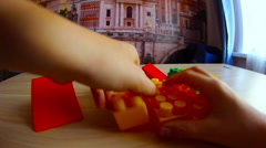 Little boy playing  in the colored blocks sitting at the table Stock Footage