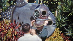 1959: Brothers trying on old underwater divers helmet. Stock Footage