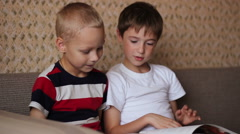 Two boys  sitting on a couch and read a book smiling Stock Footage