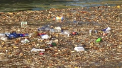 Litter, pet bottles and beverage cans, floats on water surface - full screen Stock Footage